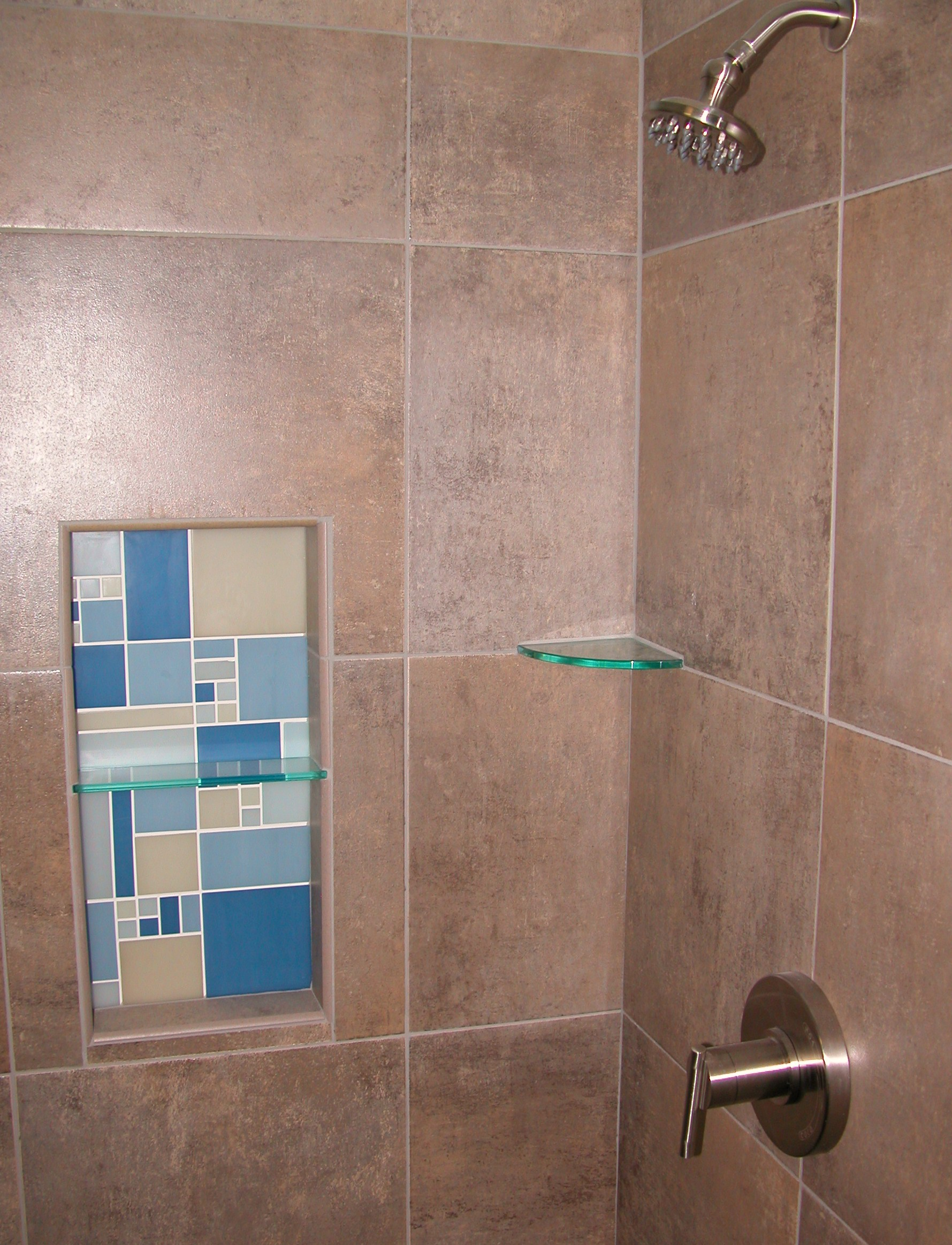 Tiled shower with mosaic niche and frameless shower door